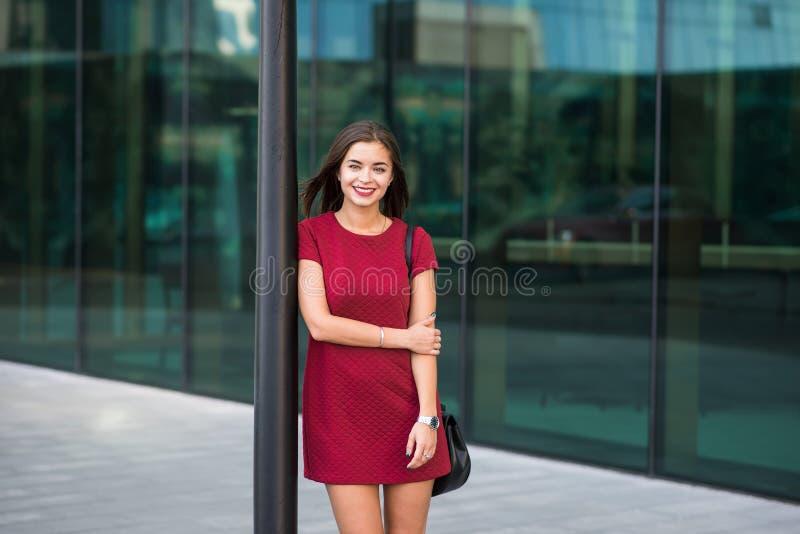 Het halve lengteportret van een jonge vrolijke succesvolle onderneemster kleedde zich in klassieke elegante kleren die stellen, stock afbeelding