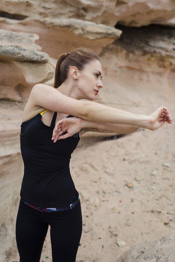 Het halve lengteportret van jong wijfje jogger gekleed in sportslijtage het doen bewapent in openlucht uitrekkende oefening in aa stock afbeeldingen