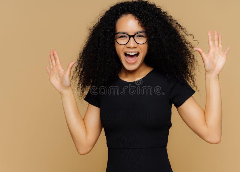 Het halve lengteschot van tevreden extatische vrouw danst zich positief en beweegt, opheft palmen, uitroept met geluk, draagt zwa stock foto