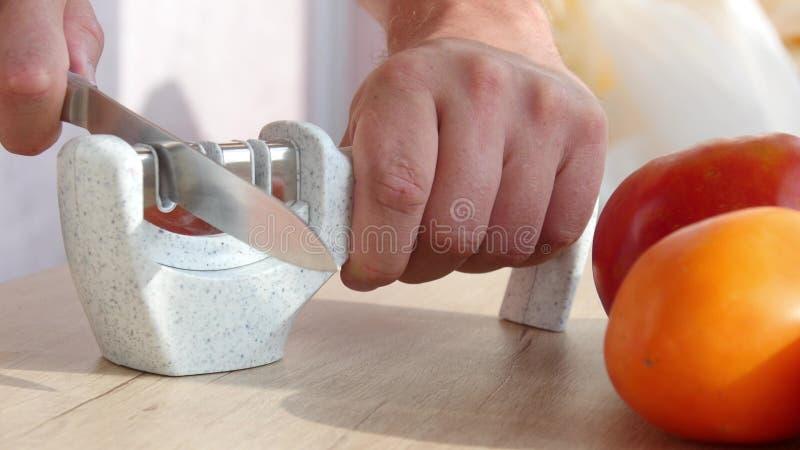 Het hand scherpen van een mes in een speciale slijper royalty-vrije stock foto