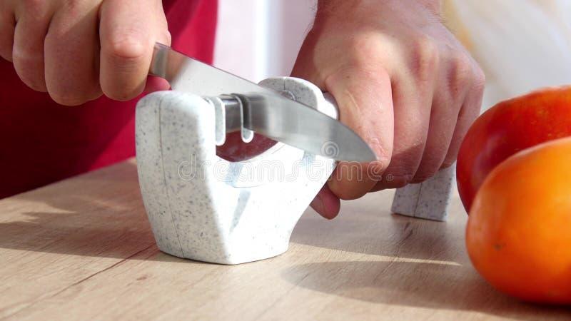 Het hand scherpen van een mes in een speciale slijper stock afbeeldingen