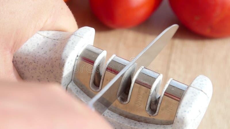 Het hand scherpen van een mes in een speciale slijper stock fotografie