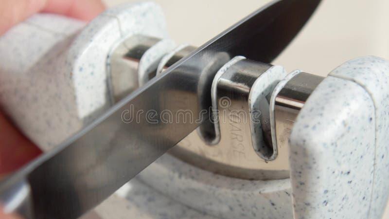 Het hand scherpen van een mes in een speciale slijper stock foto's