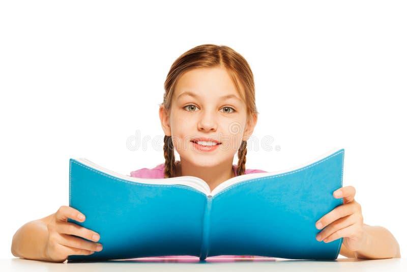 Het handboek van de schoolmeisjeholding in haar handen royalty-vrije stock afbeelding