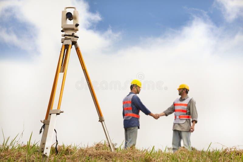Het handenschudden van twee Landmetersingenieurs op het gebied stock fotografie