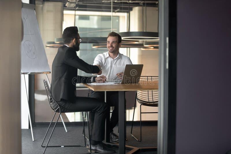 Het handenschudden van zakenliedenpartners op vergadering in bestuurskamer stock fotografie