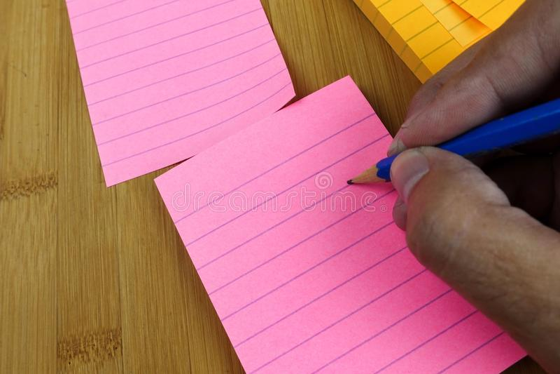 Het handpotlood schrijft in een lege roze blocnote royalty-vrije stock afbeeldingen