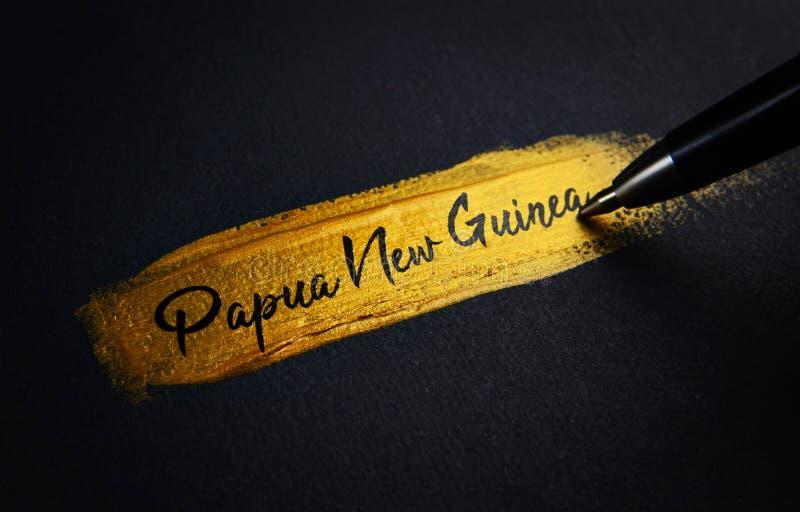 Het Handschrifttekst van Papoea-Nieuw-Guinea op de Gouden Slag van de Verfborstel stock foto's