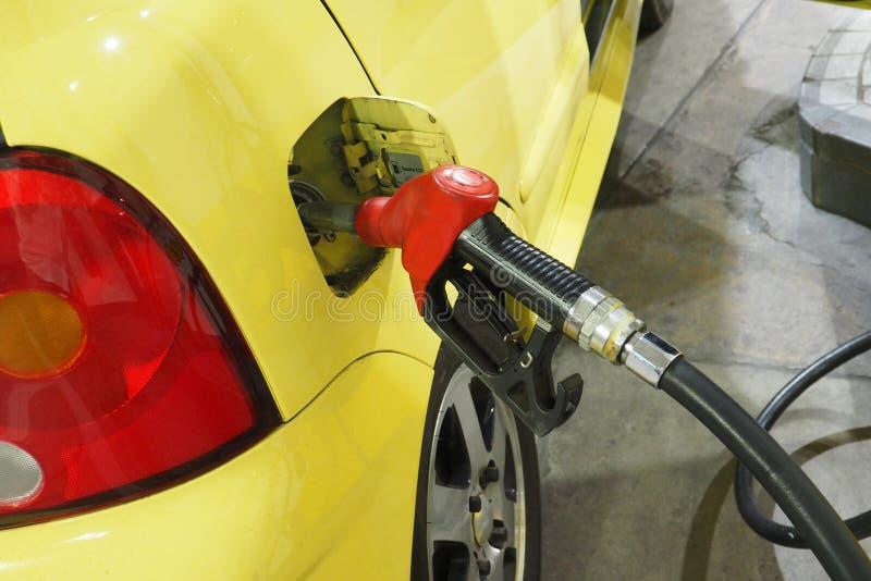Het handvat en het dienen Gasohol van de pijpbrandstof binnen aan de auto stock afbeelding