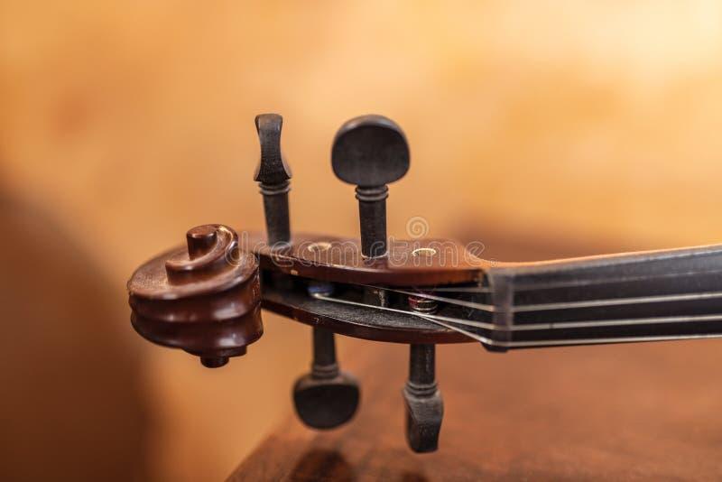 Het handvat van het vioolinstrument met koorden en stemmende pinnen onder warm licht royalty-vrije stock fotografie