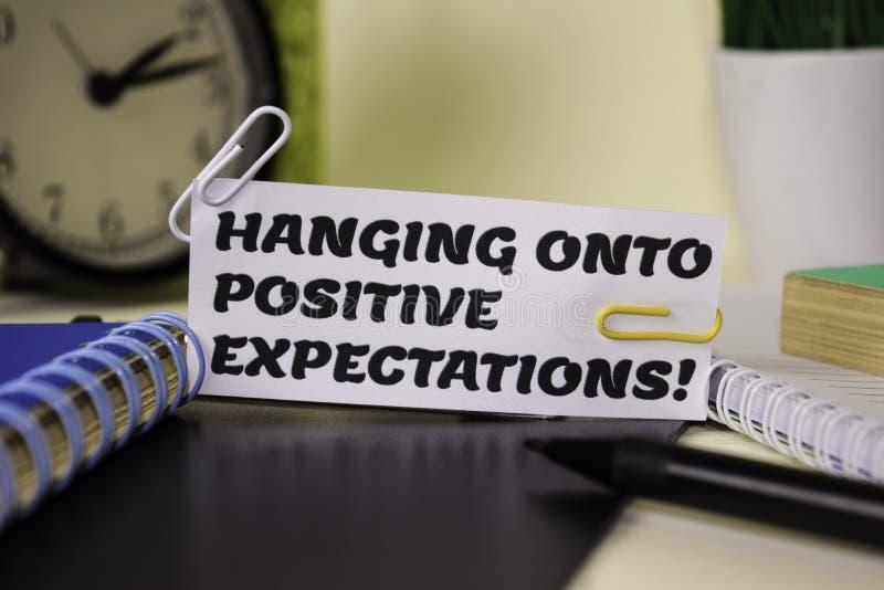 Het hangen op Positieve die Verwachting op het document op het bureau wordt geïsoleerd Bedrijfs en inspiratieconcept stock foto's