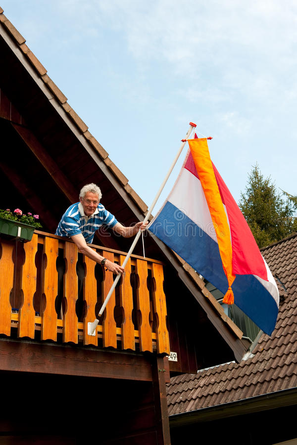 Het hangen van de Nederlandse vlag stock afbeeldingen