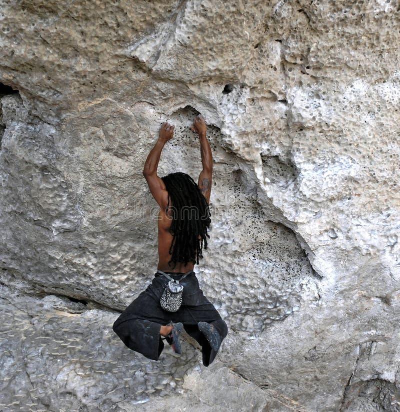 Het hangen van Rockclimber van rots stock afbeeldingen