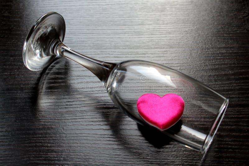 Het hart is binnen het overgehelde glas stock afbeelding