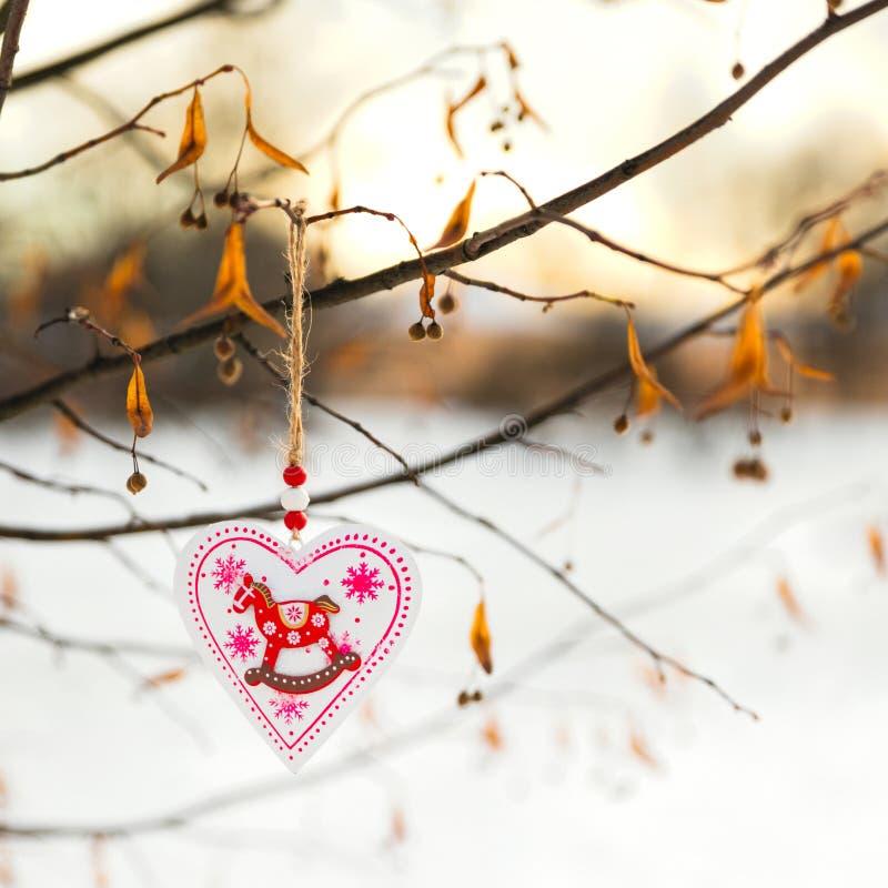 Het hart gaf Valentijnskaarten of het stuk speelgoed van de Kerstmisdecoratie het hangen op de boomtak met gestalte sneeuw op de  royalty-vrije stock afbeeldingen