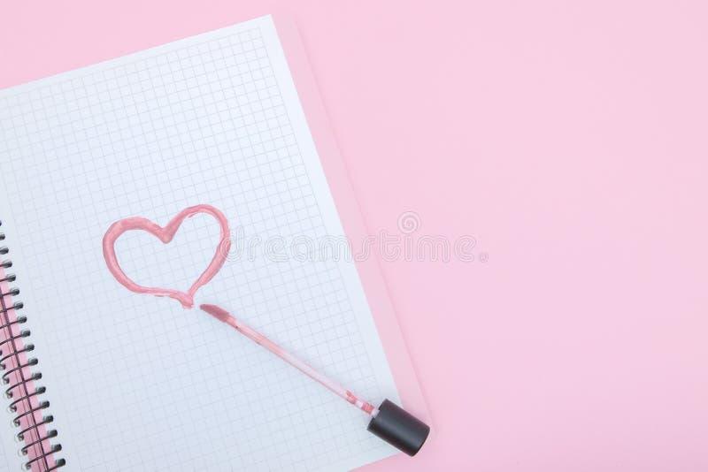 Het hart is geschilderd met een lippenstift in een notitieboekje op een roze achtergrond Liefde en Schoonheidsconcept stock afbeelding