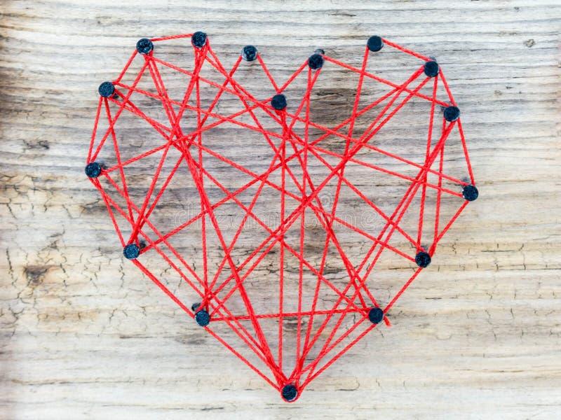 Het hart handcrafted met spijkers en rode lijn royalty-vrije stock foto's