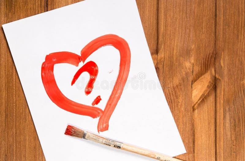Het hart met rode verf op een schoon blad van document met a wordt getrokken die stock foto
