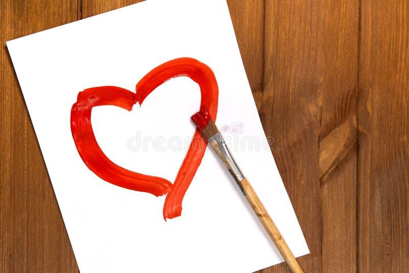 Het hart met rode verf op een schoon blad van document wordt getrokken dat royalty-vrije stock afbeelding