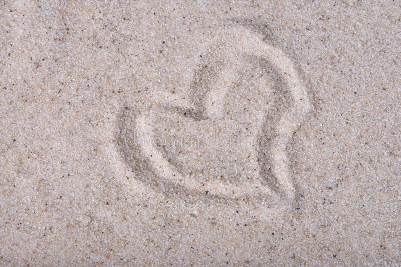 Het hart op overzees zand wordt getrokken, sluit omhoog mening die royalty-vrije stock afbeeldingen