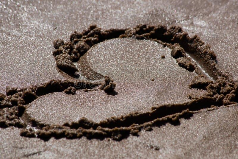 Het hart op zand wordt getrokken dat is dicht stock fotografie