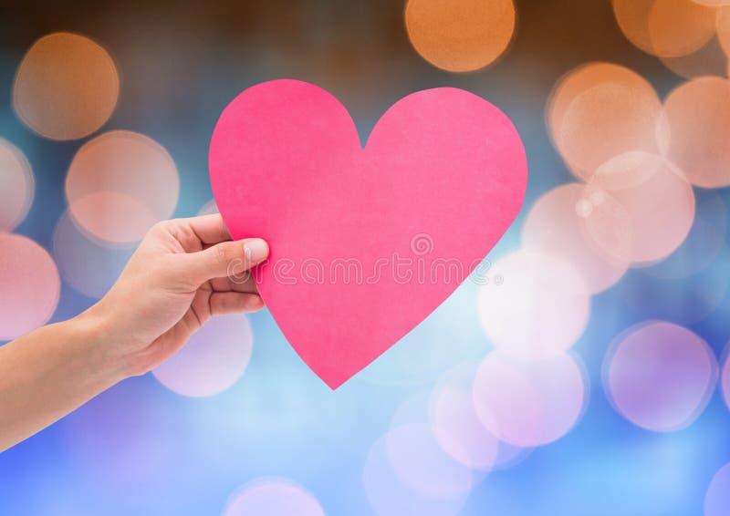 Het hart van de handholding met fonkelende lichte bokehachtergrond royalty-vrije stock afbeelding