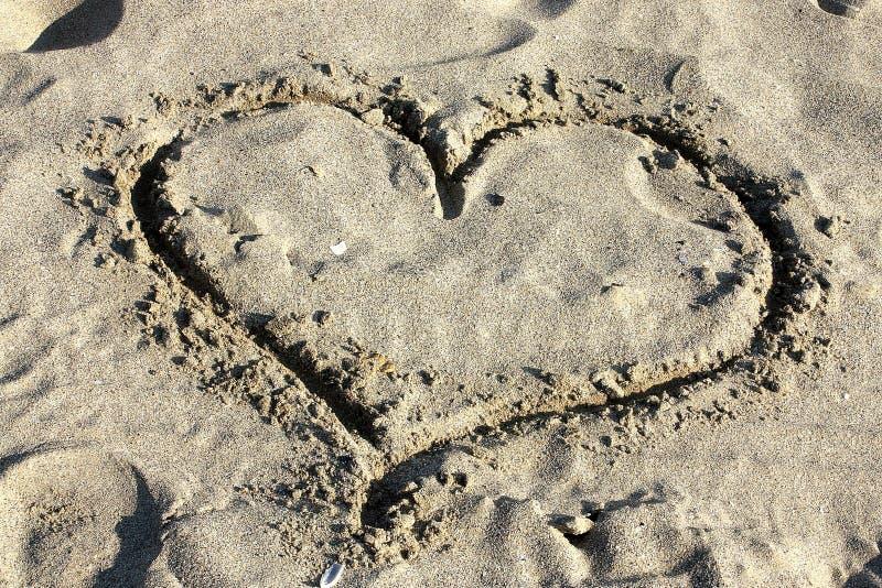 Het hart van de liefde dat in zand wordt getrokken stock afbeelding