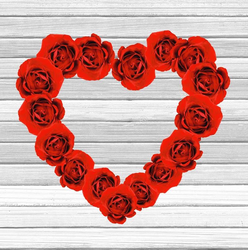 Het hart van de valentijnskaartendag van rode rozen op witte houten backgroun wordt gemaakt die royalty-vrije stock afbeelding
