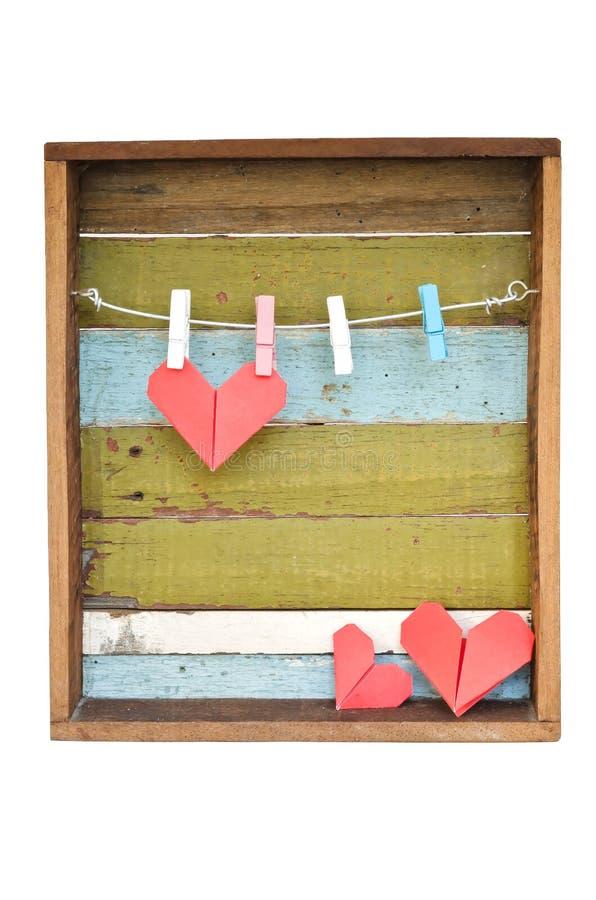 Het hart van het document het hangen op de drooglijn. Op oude houten achtergrond. stock afbeeldingen