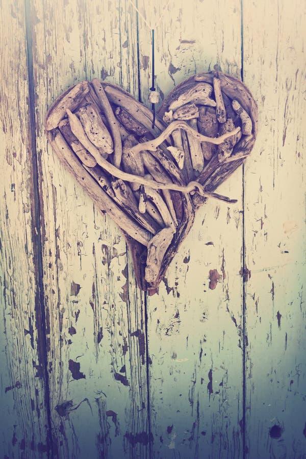 Het hart van het drijfhout op uitstekende muur stock afbeeldingen