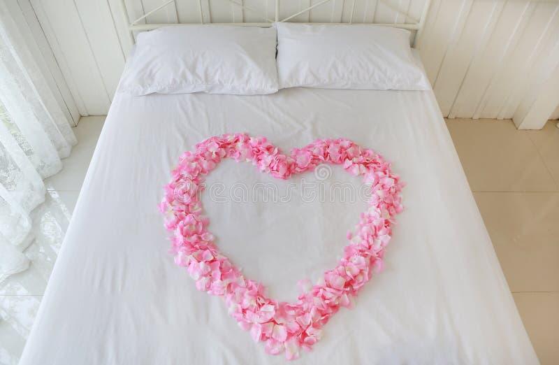 Het hart van kunstmatige roze nam bloemblaadjes op een bed toe honeymoon stock afbeelding