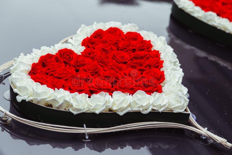 Het hart van rode en witte rozen wordt gemaakt ligt op de zwarte kap die stock fotografie