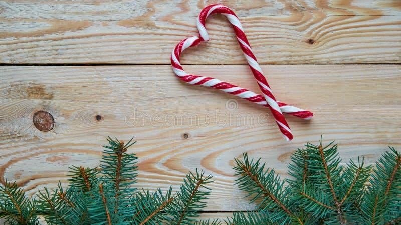 Het hart van twee rode die suikergoedkegels met Kerstboom worden verfraaid vertakt zich op de houten achtergrond Nieuwe jaar of v royalty-vrije stock afbeeldingen