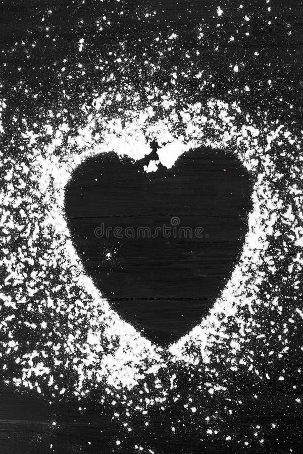 Het hart vormde gepoederde suiker op zwarte houten achtergrond stock afbeeldingen