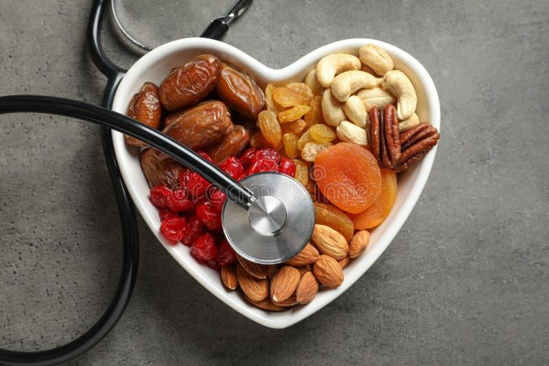 Het hart vormde kom met droge vruchten, noten en stethoscoop op grijze achtergrond stock foto