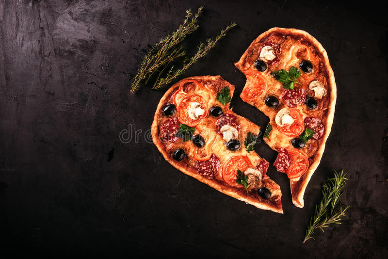Het hart vormde pizza met tomaten en mozarella voor Valentijnskaartendag op uitstekende zwarte achtergrond Voedselconcept romanti royalty-vrije stock fotografie