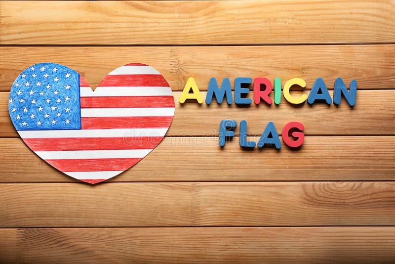 Het hart vormde tekening van Amerikaanse nationale vlag met kleurenbrieven op houten lijst stock foto's