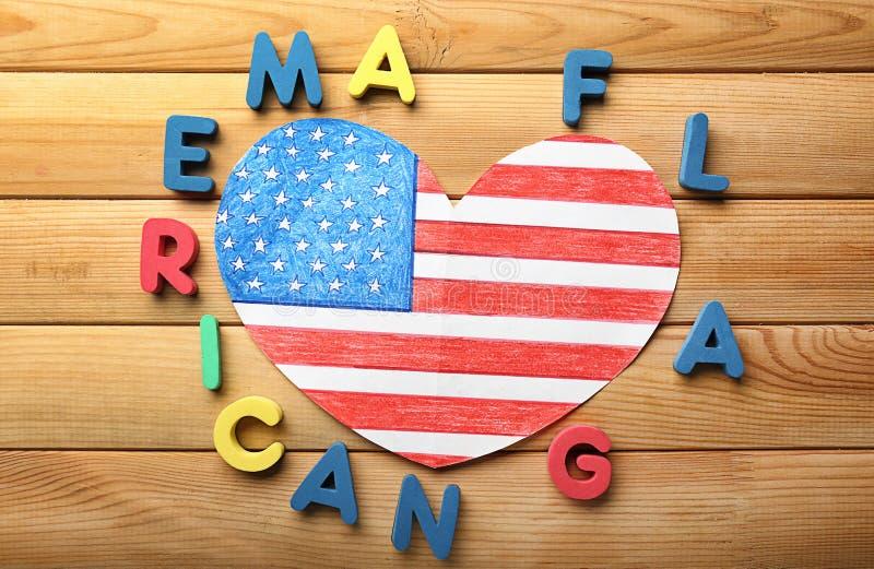 Het hart vormde tekening van Amerikaanse nationale vlag met kleurenbrieven op houten lijst stock afbeelding