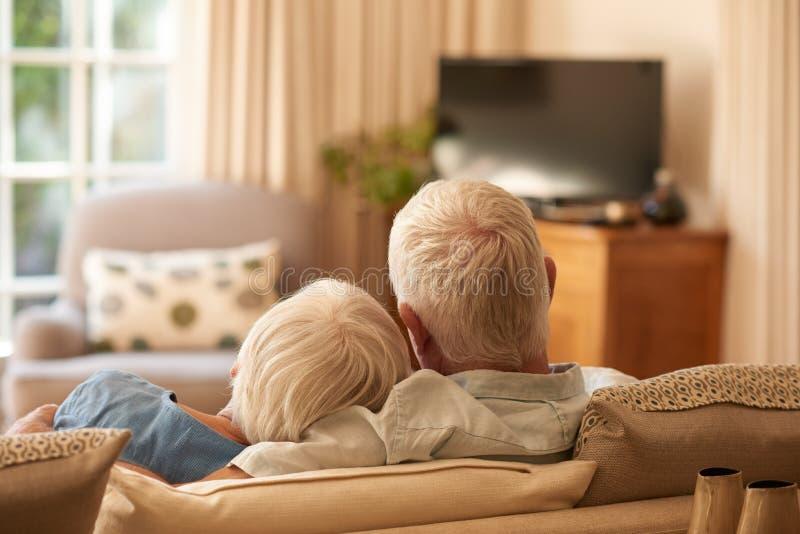 Het hartelijke hogere paar ontspannen samen op hun bank thuis royalty-vrije stock foto's