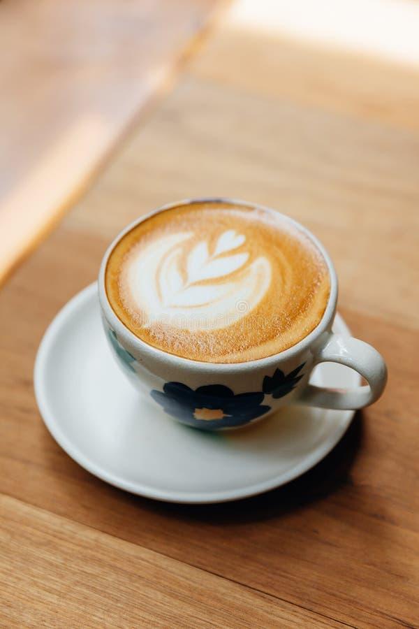 Het hartvorm van de Lattekunst die in ceramische kop op houten lijst wordt gediend royalty-vrije stock foto