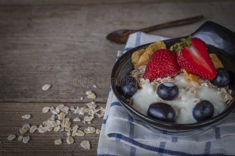 Het havermeel van de yoghurtmengeling, aardbei en druivenbovenste laagje in zwarte kom op Blauwe en witte gestreepte stof en hout royalty-vrije stock foto's