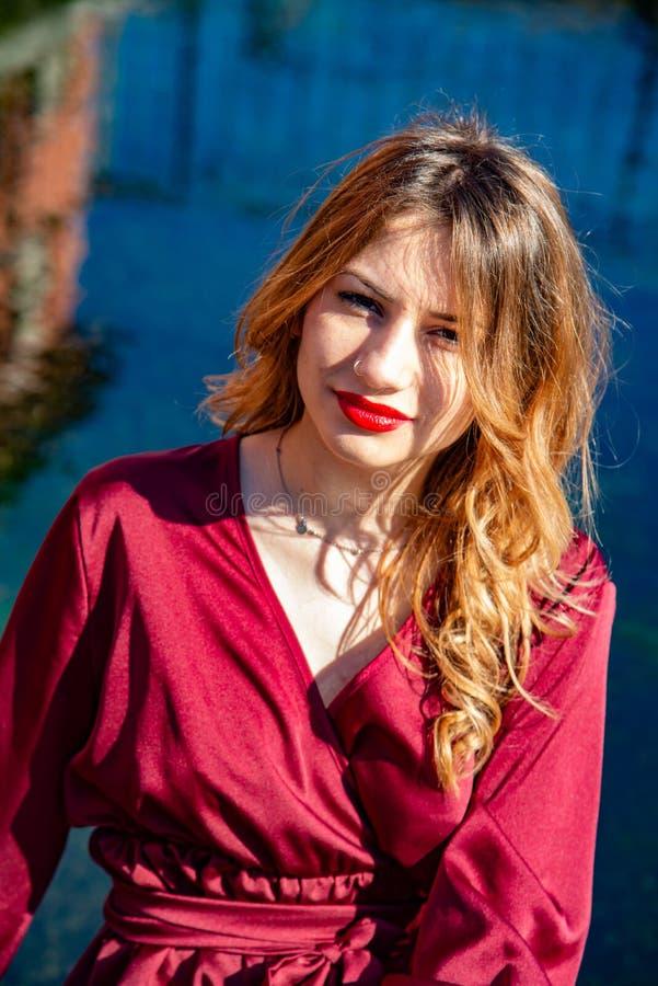 Het Headshotportret van een blondemeisje in natuurlijk licht spreidde langs de bank van een rivier uit Hij heeft rode lippen, ern royalty-vrije stock fotografie