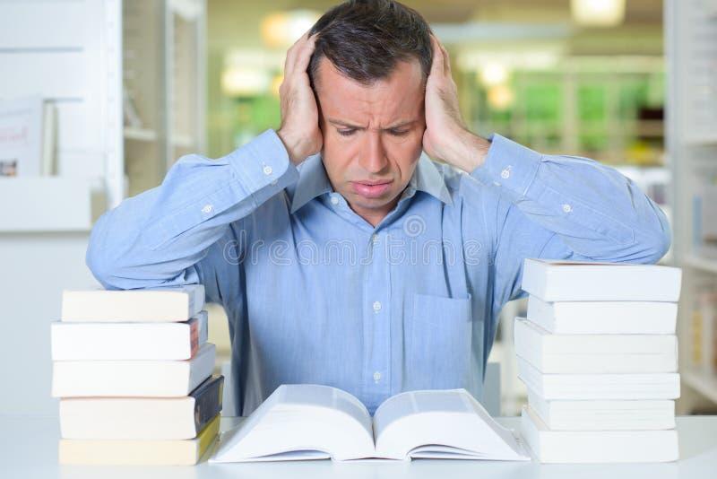 Het hebben van hoofdpijn terwijl het lezen royalty-vrije stock afbeelding