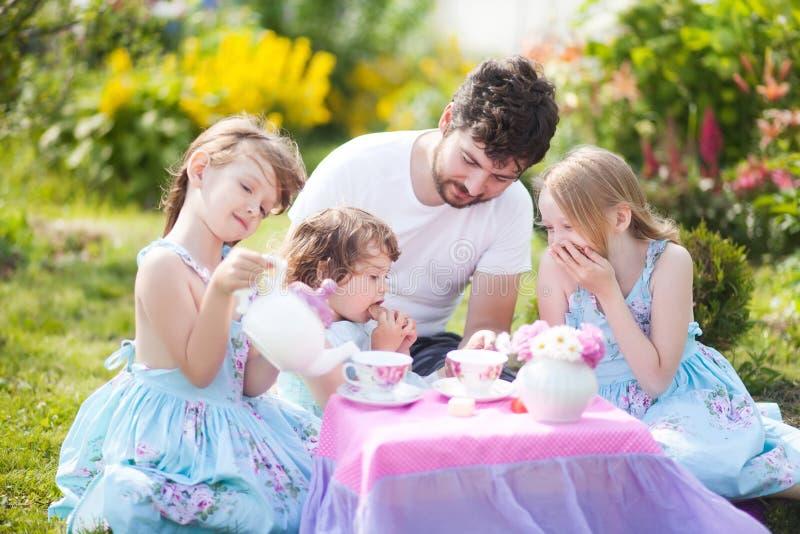 Het hebben van vele kinderenvader die theekransje met dochters betalen stock afbeelding