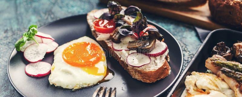 Het Heerlijke eigengemaakte ontbijt Fried Eggs van de voedselbanner, sandwich, kaas, groenten, paddestoelen, brood en kruiden stock fotografie