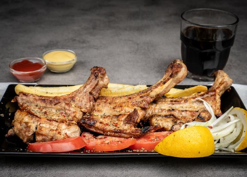 Het heerlijke Geroosterde Varkensvleeslapje vlees diende met gebraden aardappels, verse tomaten, uien en citroen stock fotografie