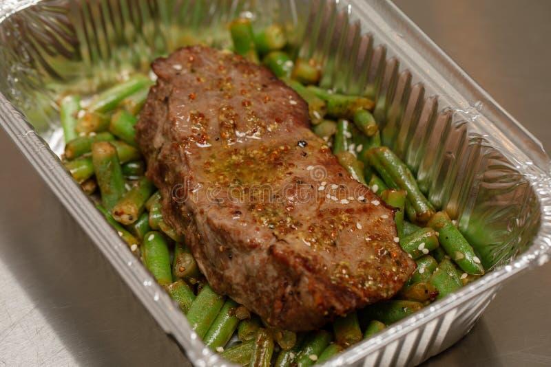 Het heerlijke meeneemvoedsel, één die maaltijd in de container van het aluminiumvoedsel wordt ingepakt - Voedsellevering en haalt stock fotografie