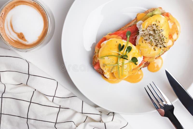 Het heerlijke ontbijt met gestroopte eieren en hollandaise saus op toost met gerookte zalm royalty-vrije stock foto's