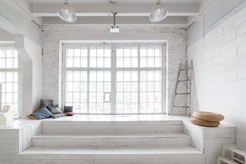 Het heldere binnenland van de fotostudio met groot venster, hoog plafond, witte houten vloer stock foto