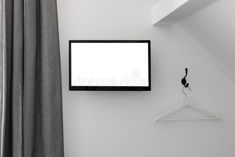 Het heldere binnenland van de zolderslaapkamer met TV op de muur stock foto's